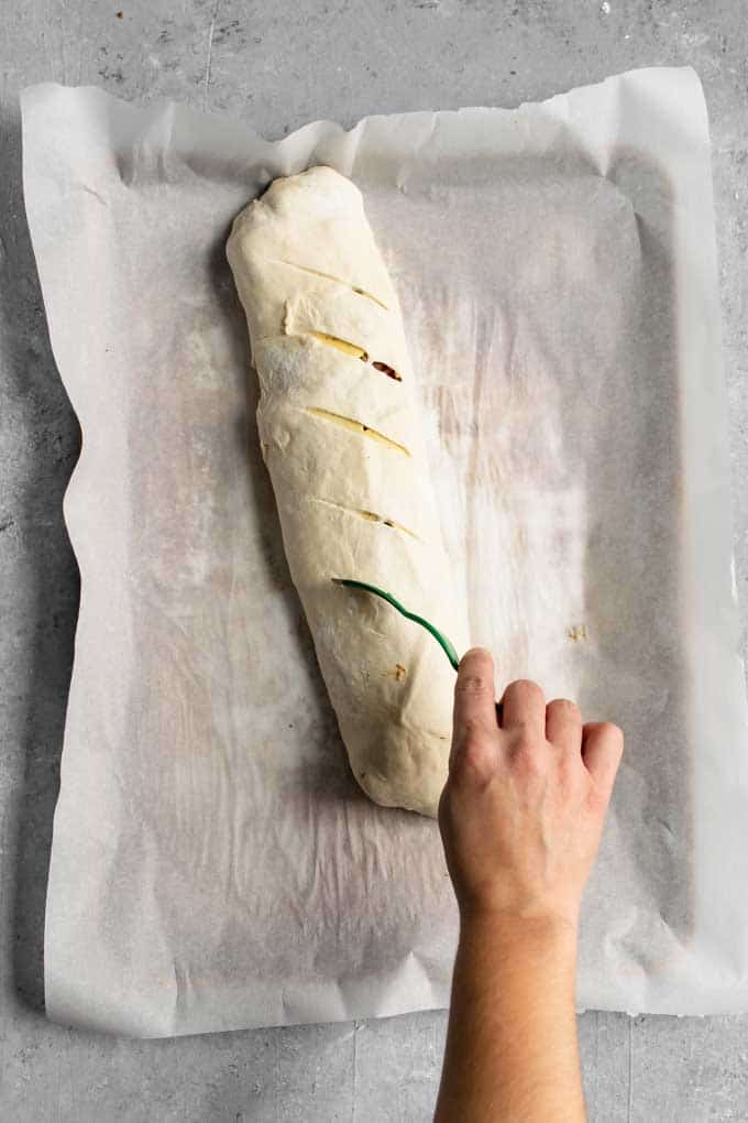 slicing the slits into the top of the stromboli with a bread lame