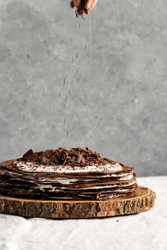 sprinkling chocolate shavings over a boozy vegan chocolate crepe cake