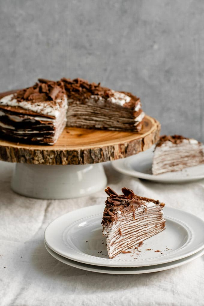 slices of vegan dark chocolate crepe cake with whipped whiskey cream