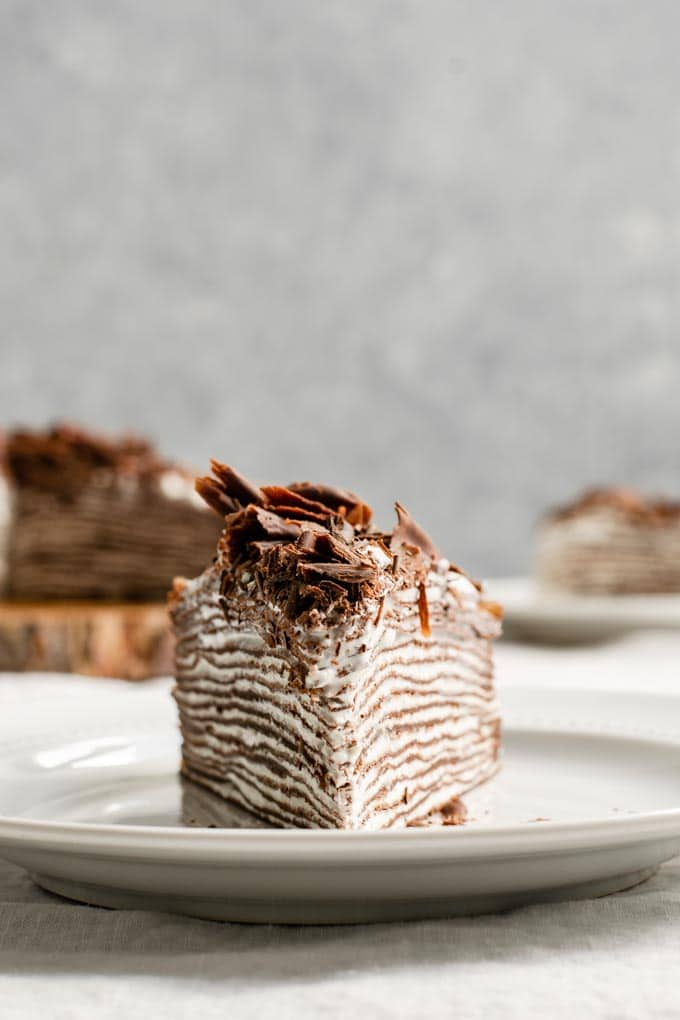 slice of vegan chocolate crepe cake with whipped cream filling