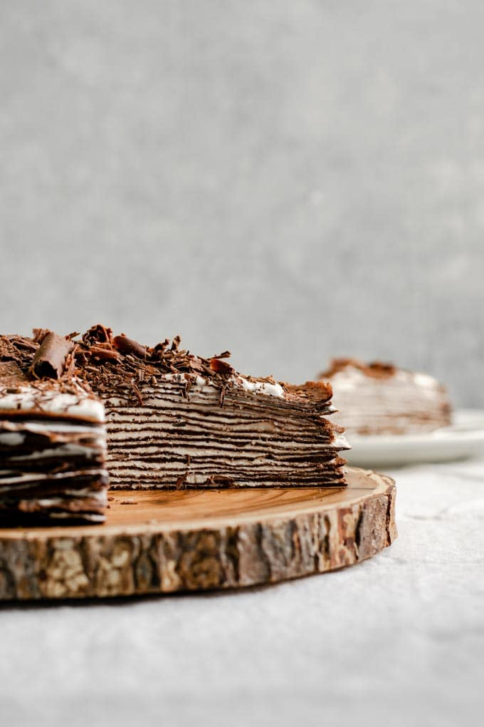 slices cut out of chocolate crepe cake with whipped cream filling to show layers