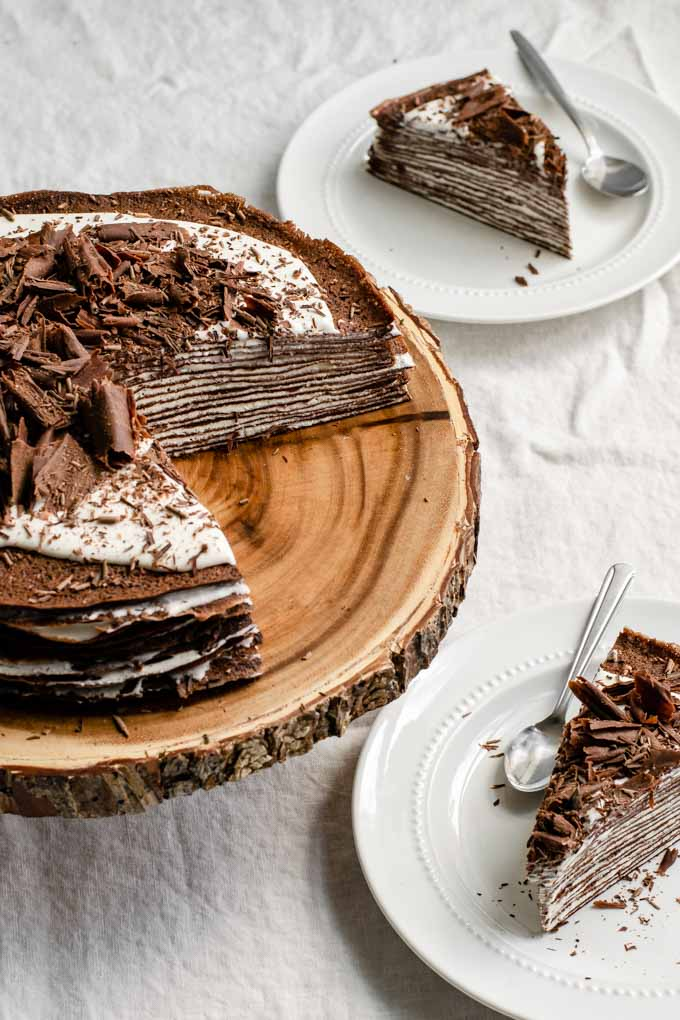 angled view of vegan dark chocolate crepe cake with whipped cream filling