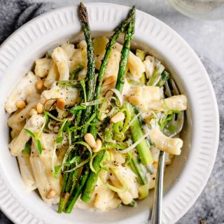 a bowlful of creamy asparagus and leek pasta served with a glass of wine