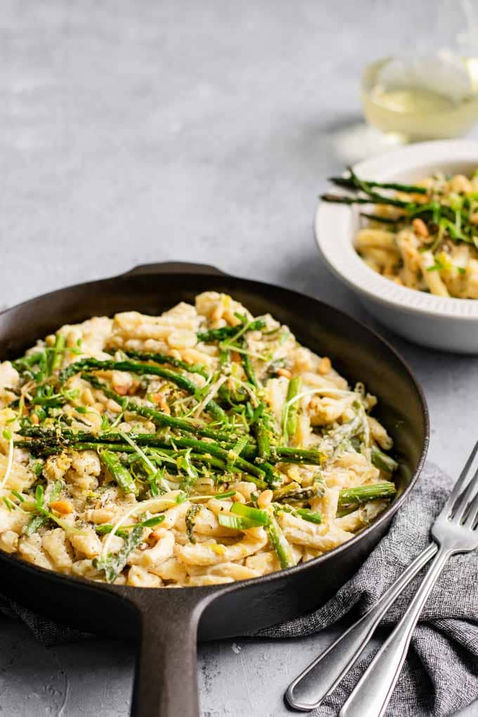 asparagus and leek pasta in a cast iron skillet with a bowl served along with a glass of wine