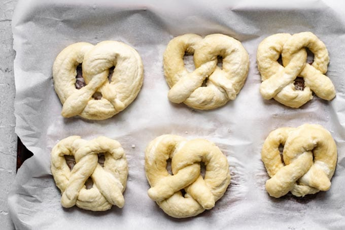 homemade soft pretzels shaped and boiled in a baking soda bath and ready to bake