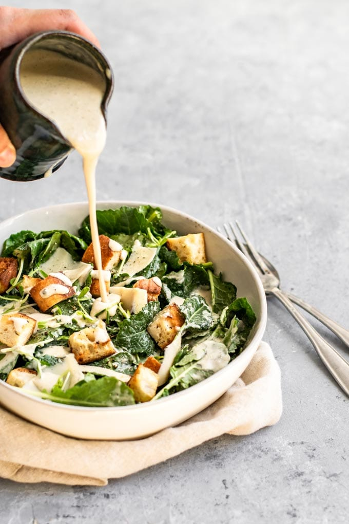 pouring vegan classic caesar salad dressing over baby kale and crouton salad