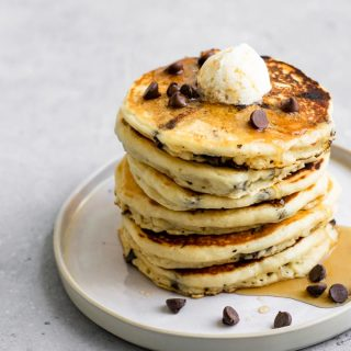 a stack of vegan chocolate chip panckes topped with vegan butter, chocolate chips, and maple syrup