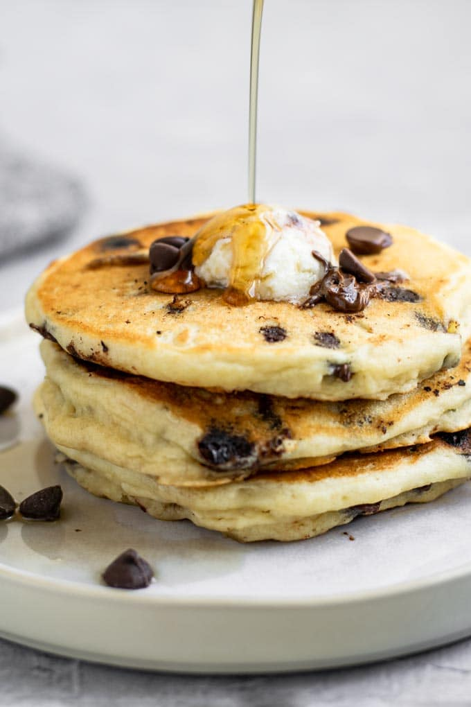 3 chocolate chip pancakes stacked with maple syrup being drizzled over top