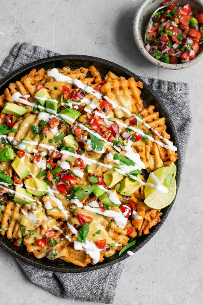 waffle fry nachos with homemade vegan queso and served with pico de gallo