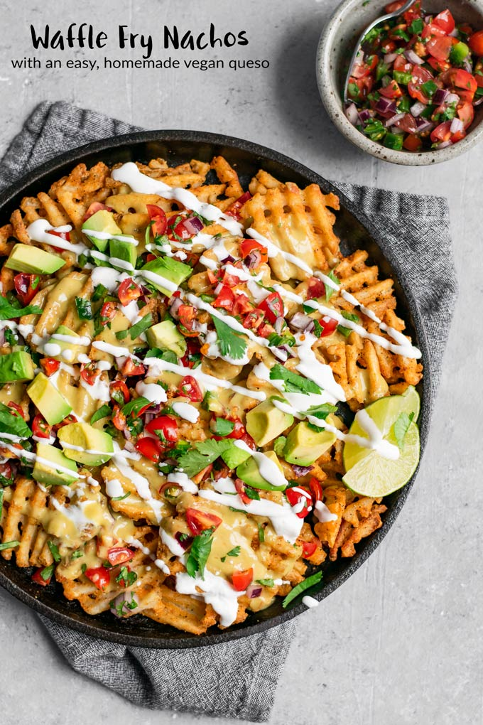 These waffle fry nachos are smothered in an easy homemade vegan queso and topped with fresh pico de gallo, sour cream, and avocado for a delicious gluten free snack or meal! #thecuriouschickpea #vegan #glutenfree #nachos #fries #wafflefries #veganqueso