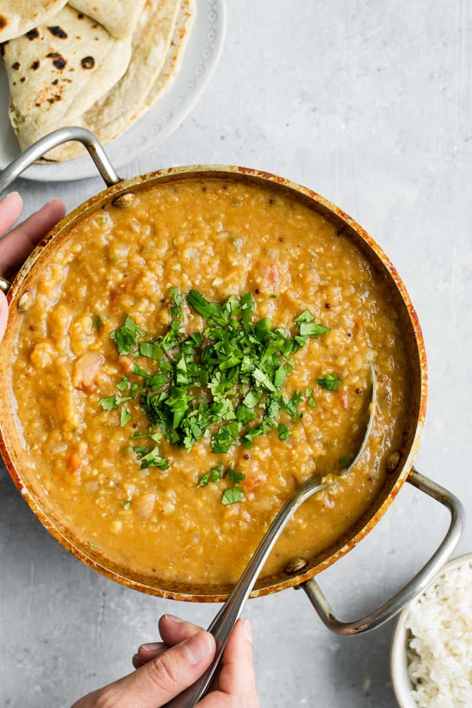 hands spooning red lentil dal tadka to serve with basmati rice and chapati