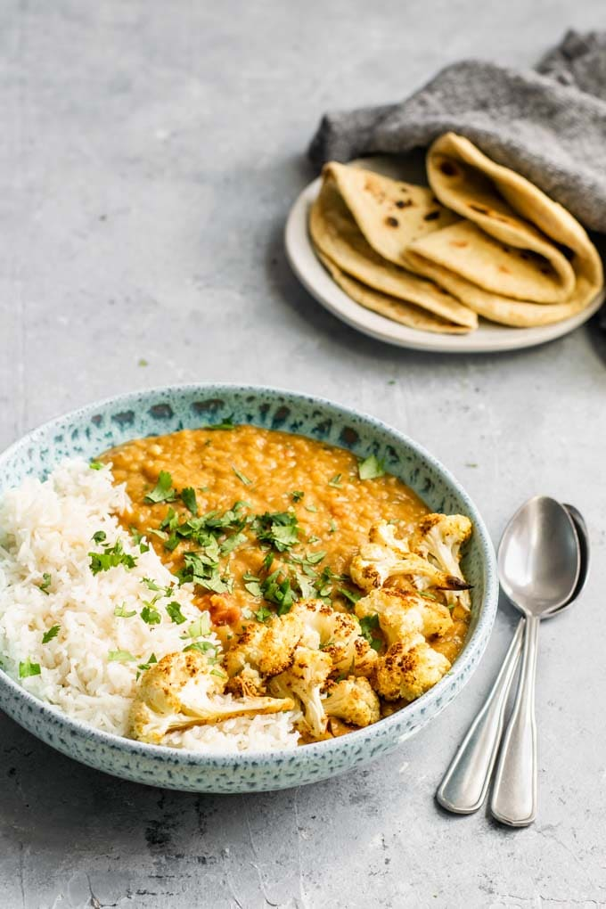 a bowl of masoor dal tadka with basmati rice and roasted cauliflower, served with chapati
