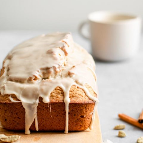 side on view of vegan chai spice loaf cake with the chai glaze dripping down the sides and a mug of chai in the background