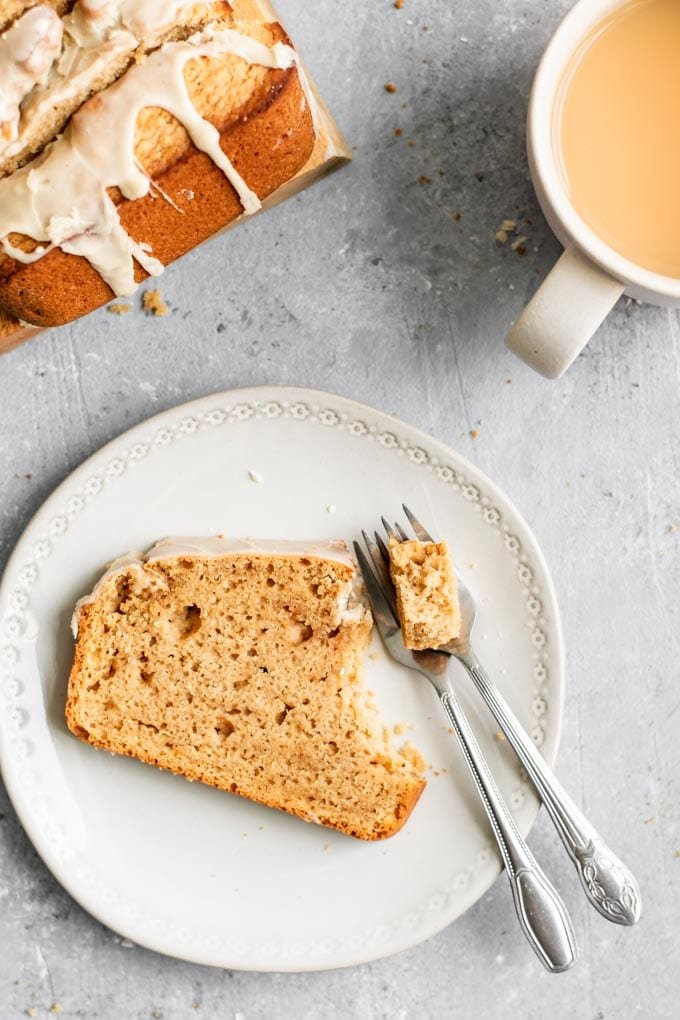 A slice of chai spice loaf cake with a fork taking a bite out of it