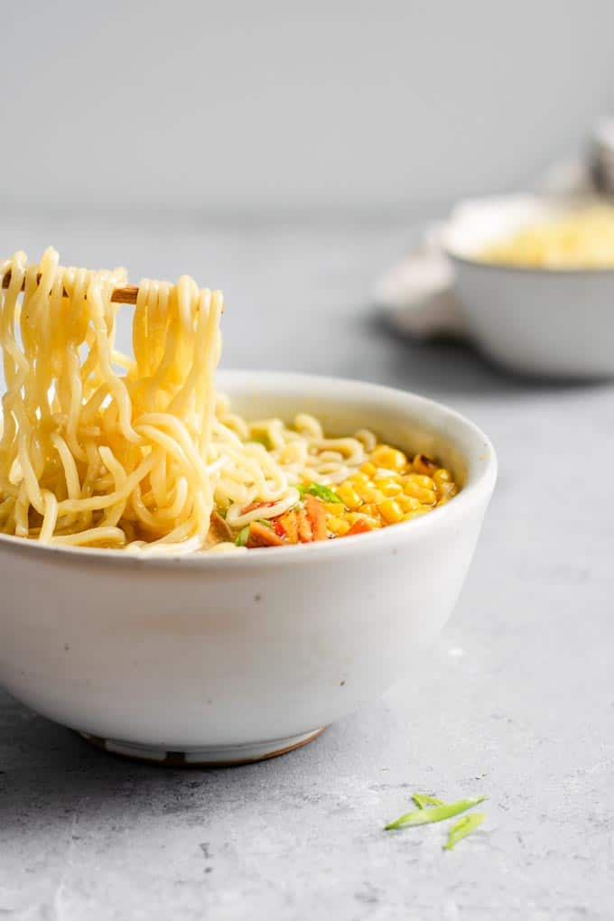 angled view of a bowl of ramen, with the noodles being lifted on chopsticks above the bowl