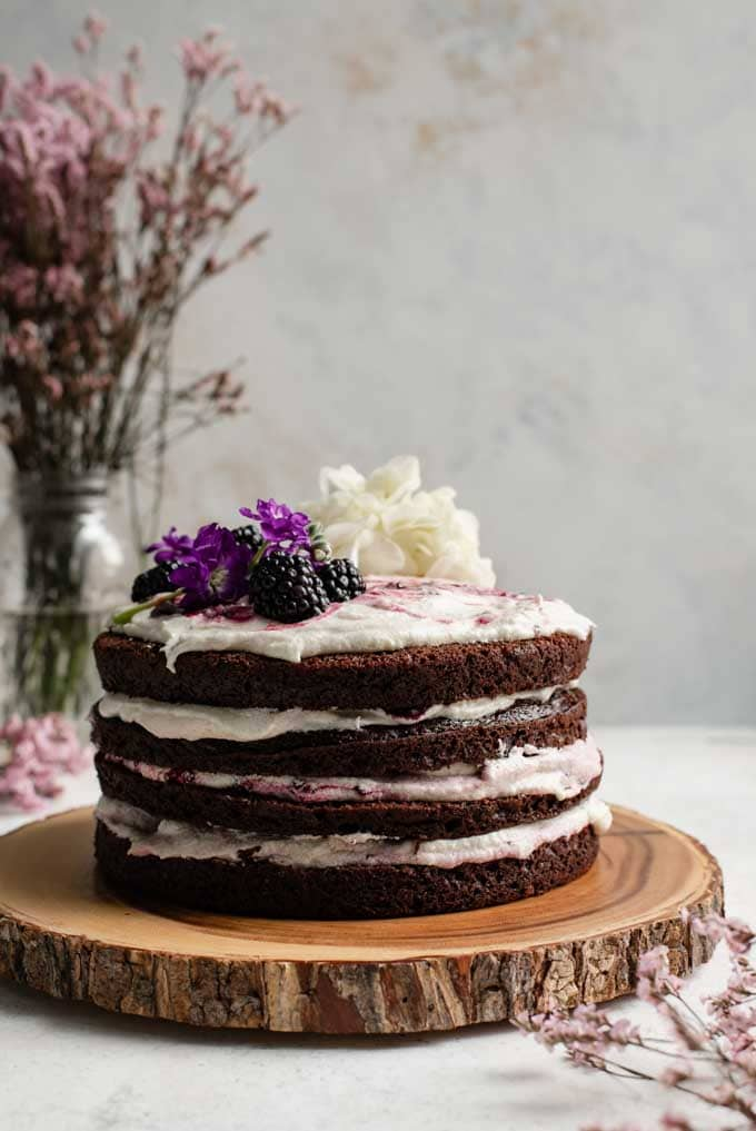 blackberry lavender chocolate cake with blackberry lavender jam, flour buttercream, and decorated with fresh blackberries and flowers