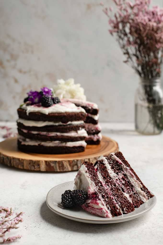 slice of blackberry lavender chocolate cake with the whole cake in the background