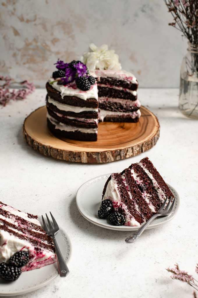 two slices of cake on plates with the whole blackberry lavender chocolate cake in the background