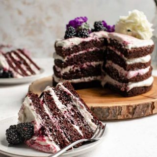 vegan blackberry lavender chocolate cake, with a slice cut out and served on a plate