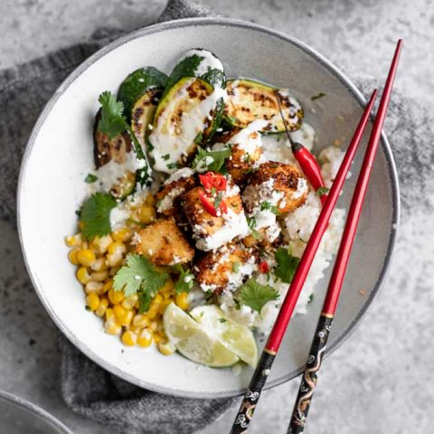 crispy coconut tofu poke bowl with wasabi sauce drizzled overtop and red chopsticks