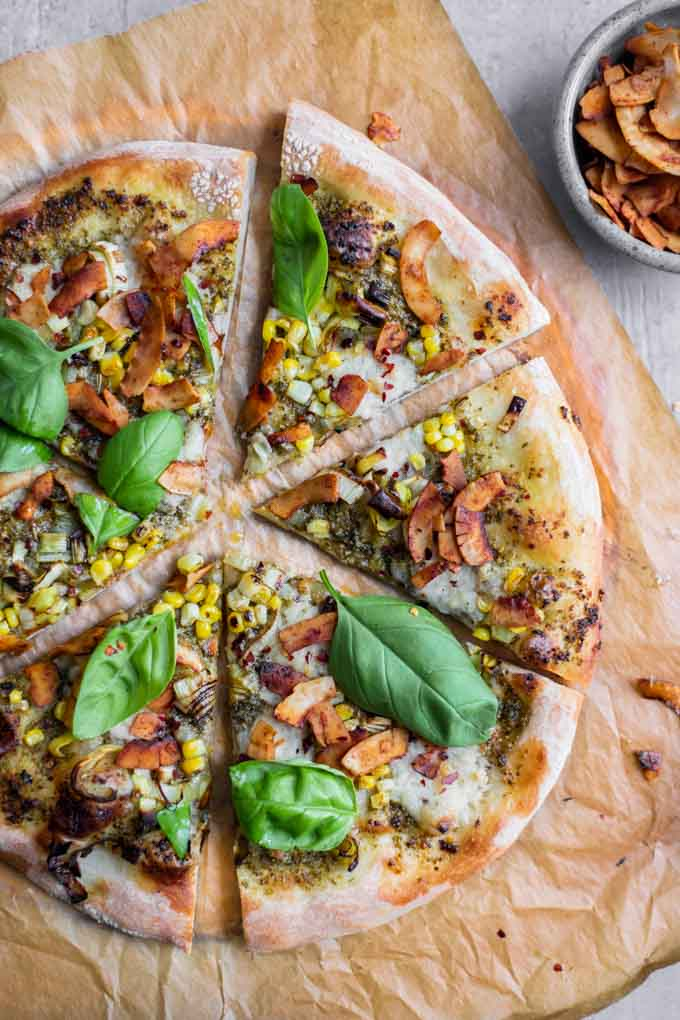 overhead view of sliced pesto leek pizza with coconut bacon on parchment paper