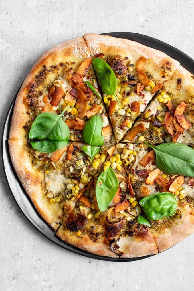 vegan pesto leek pizza on a black plate