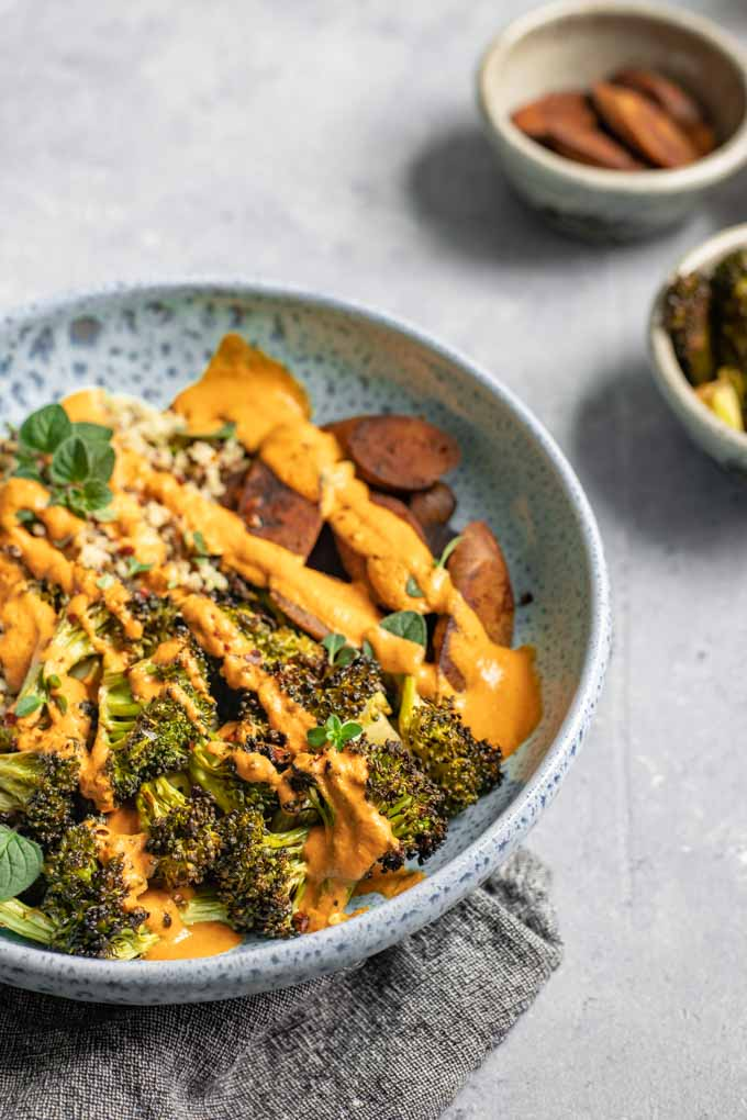 Roasted broccoli buddha bowl drizzled with red pepper sauce, extra roasted broccoli and vegan sausage on the side