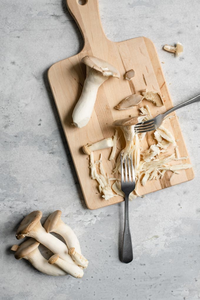 shredding king oyster mushrooms between two forks