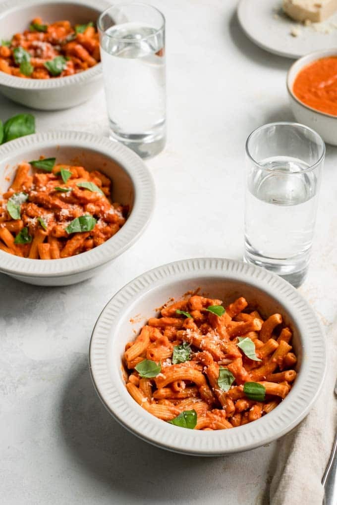 three bowls of pasta with vegan vodka sauce, topped with basil