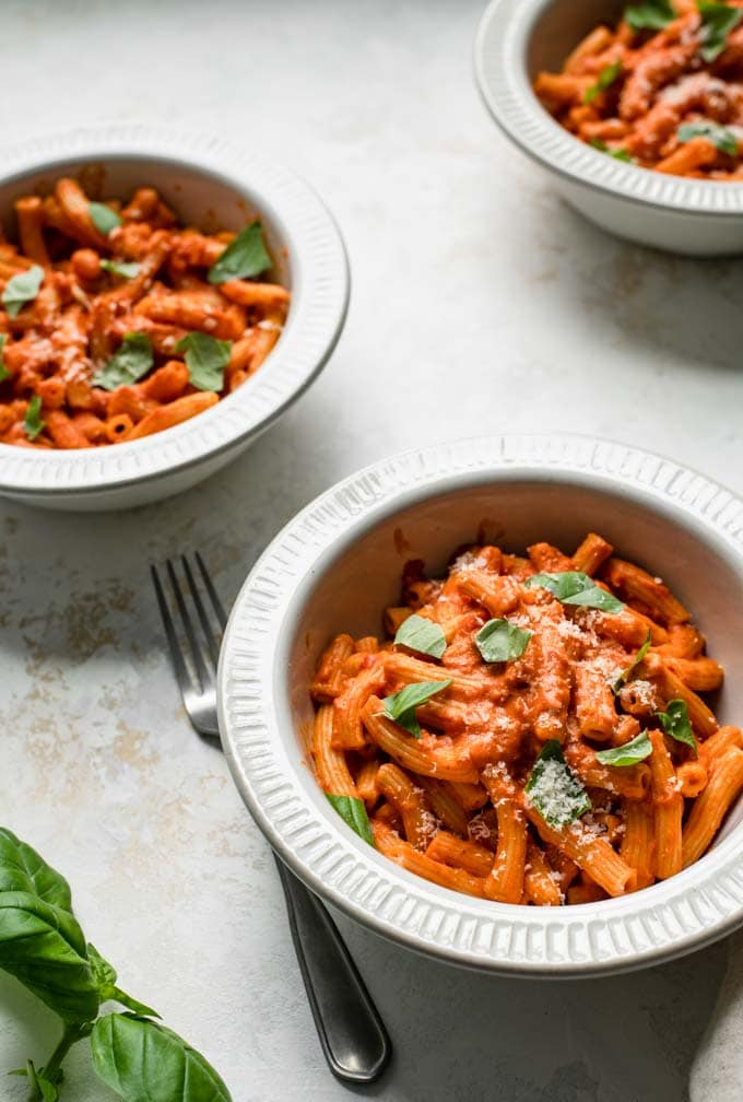 close up angled shot of three bowls filled with pasta with vegan vodka sauce,