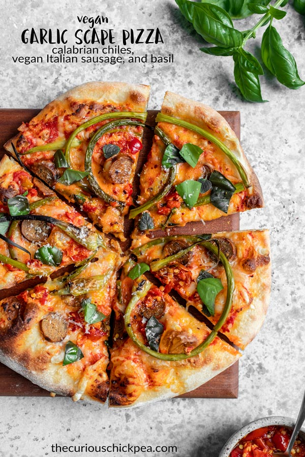 A delicious vegan garlic scape pizza topped with calabrian chiles and vegan italian sausage. | thecuriouschickpea.com #veganpizza #vegan #pizza #garlicscapes #vegancheese