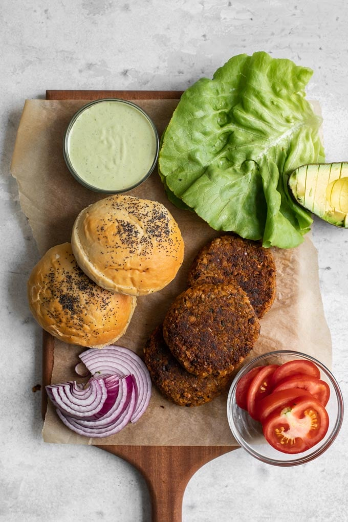 overhead view of all the items needed to build the veggie burgers: herbed chickpea burgers, buns, red onion, lettuce, tomato, pesto cashew aioli, and avocado