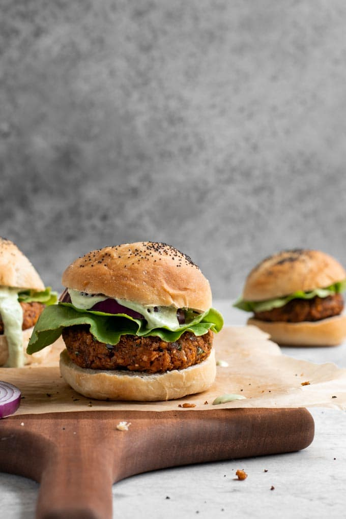 herbed chickpea burgers served on vegan milk bread buns with lettuce, red onion, and a pesto cashew aioli