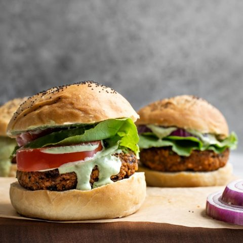 close up of herbed chickpea burgers served with a pesto cashew aioli