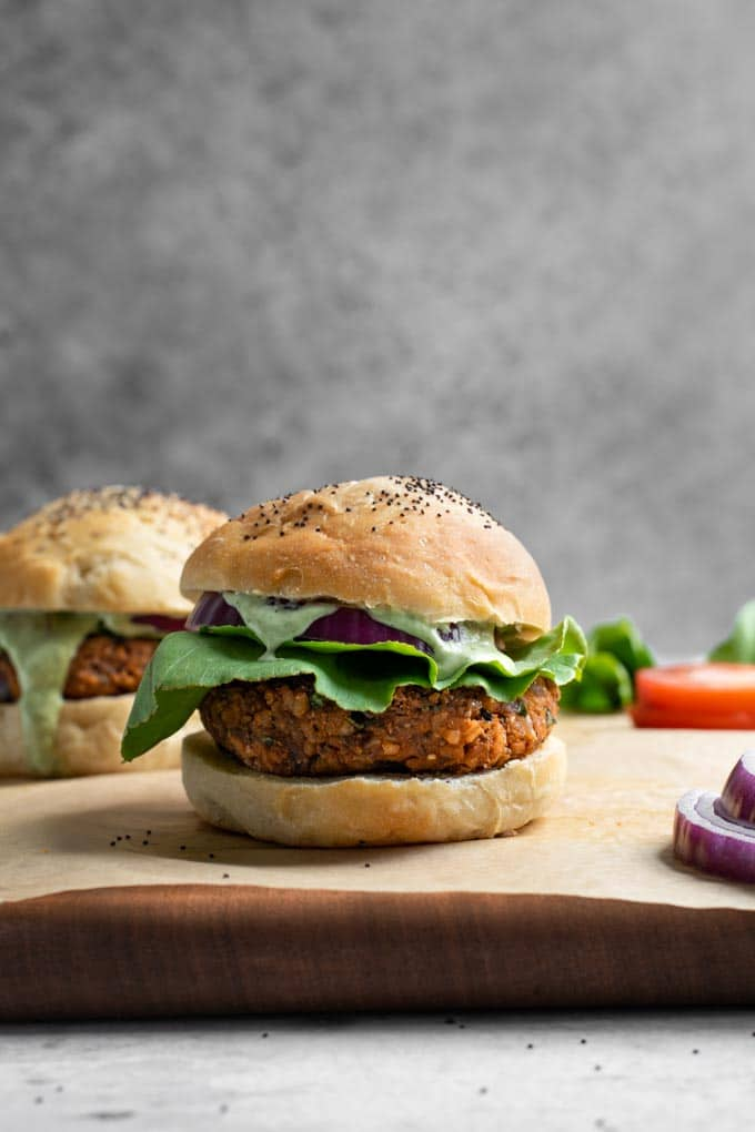 herbed chickpea burger served in a bun with lettuce, red onion, and a pesto cashew aioli dripping down. Served on a parchement lined cutting board with some sliced red onion and tomato in the photo.
