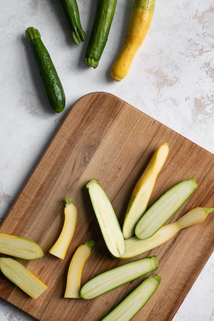 zucchini and yellow summer squash being cut in half on a cutting board