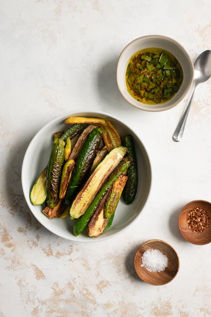 the pan fried squash in a large bowl, with the marinade mixed in a second bowl and flaked sea salt and red pepper flakes in pinch bowls
