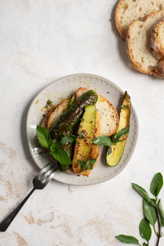 marinated zucchini with Thai basil and mint served over toast on a plate