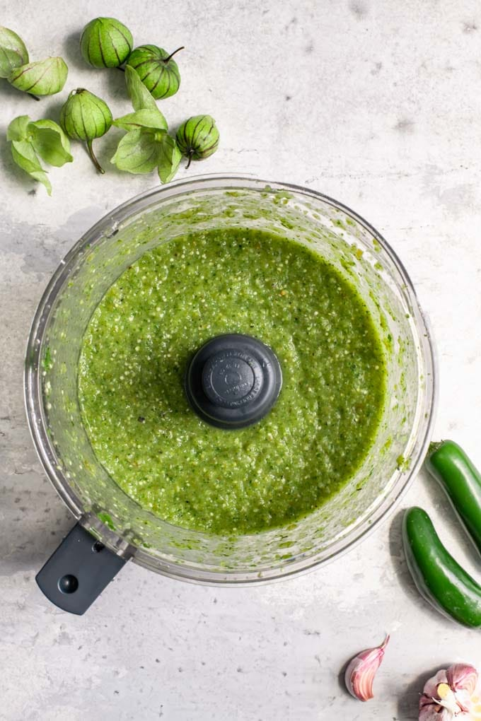 tomatillo salsa in the food processor after it has been blended to make a sauce