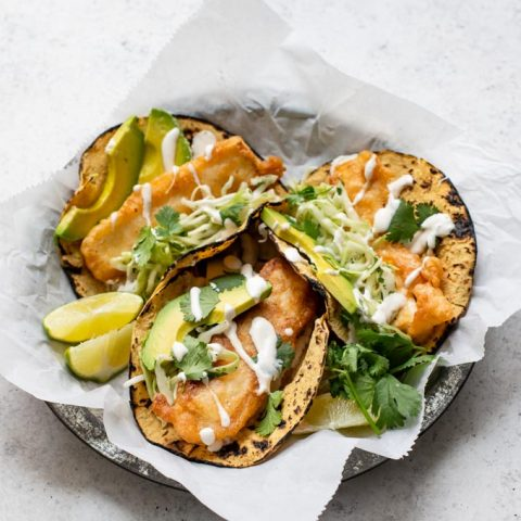 angled view of three Baja tofu tacos on a parchment lined plate