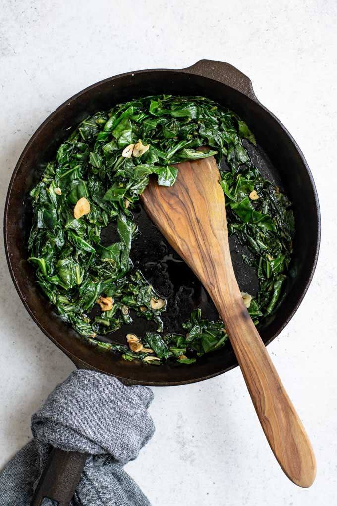 cooked smoky collard greens in a cast iron skillet after cooking