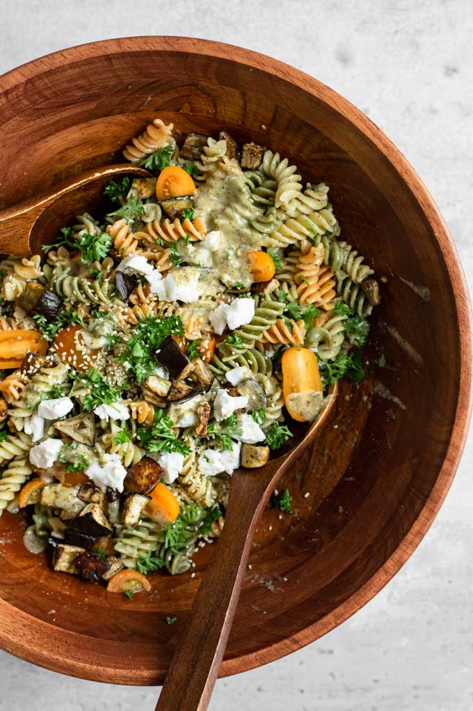 tossing together the ingredients for the pasta salad with two large wooden spoons in a wooden salad bowl