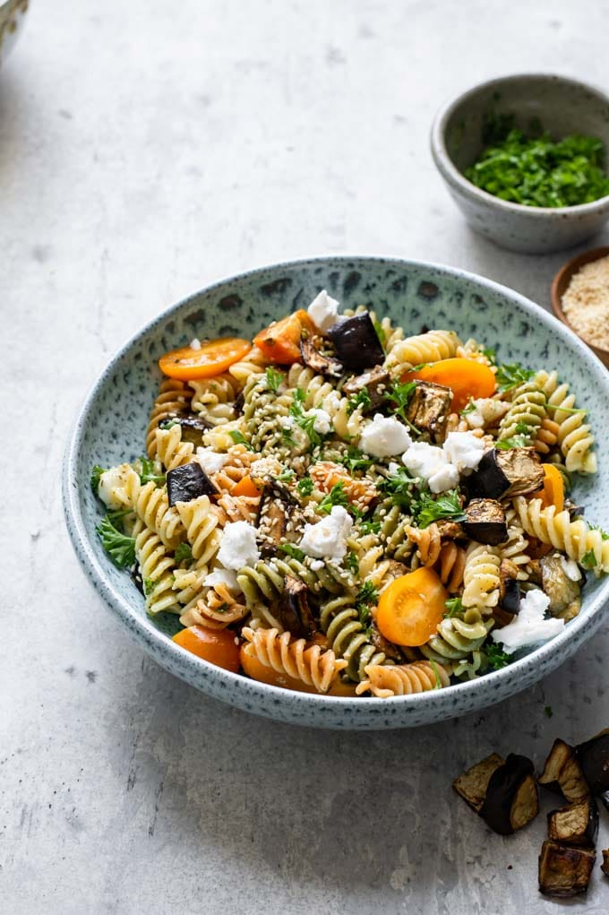 pasta salad served in a blue ceramic bowl with bowls of parsley and toasted sesame seeds on the side for garnish