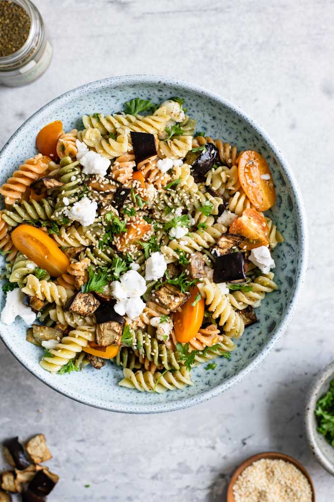 overhead view of the za'atar pasta salad served in a bowl with sides of the garnishes and eggplant on the edges of the photo
