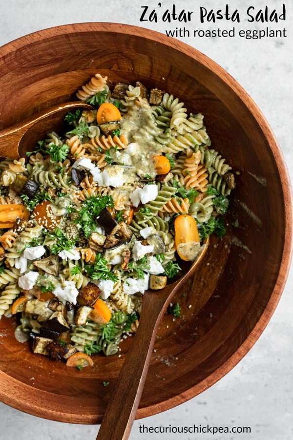 This Middle Eastern inspired za'atar pasta salad is absolutely a must make! It's made with a delicious and simple za'atar lemon vinaigrette, deeply roasted eggplant, and sweet cherry tomatoes. It's completely vegan and can be made gluten free! It's perfect for potlucks, picnics, or hot summer days! #vegan #vegetarian #pastasalad #zaatar #middleeastern #veganpasta #tomatoes #vegancheese