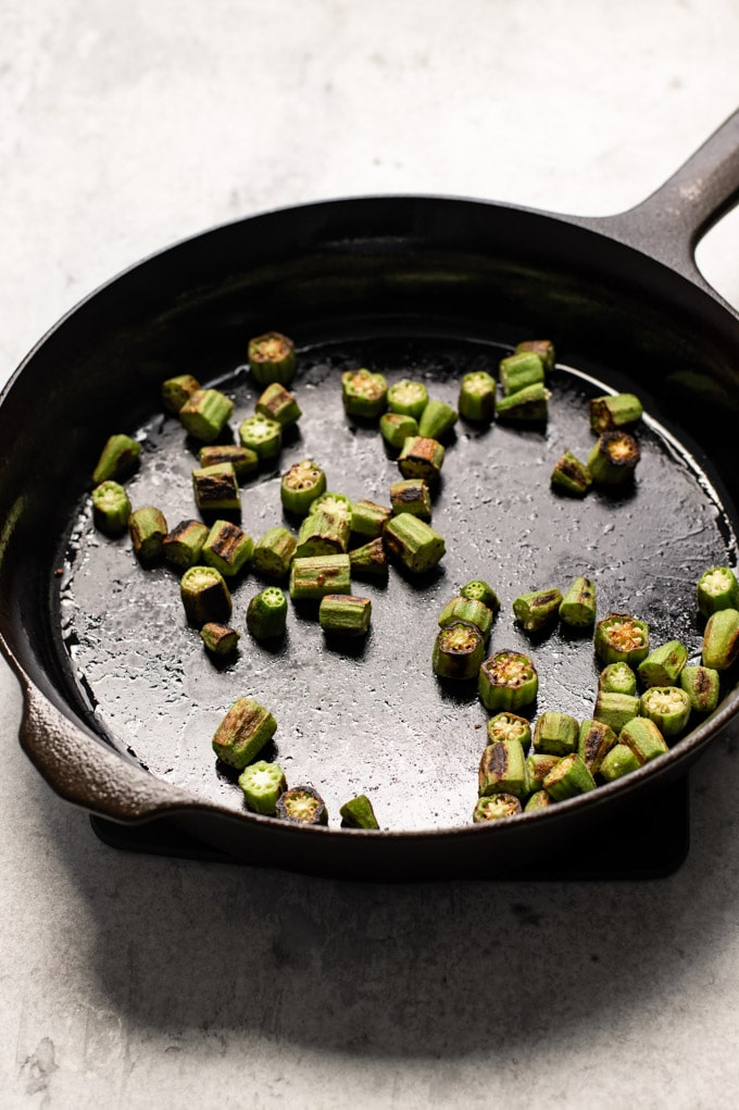 Okra cooked in the skillet right before the spices have been added, the okra has shrunk and turned golden in spots