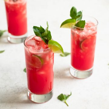 watermelon mint agua frescas in three glasses garnished with lime wedges and mint