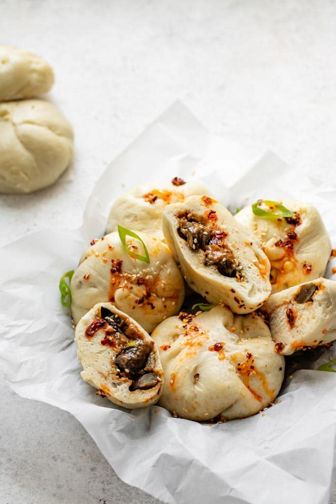 hoisin eggplant bao in a basket drizzled with chili oil with one cut open to show the filling