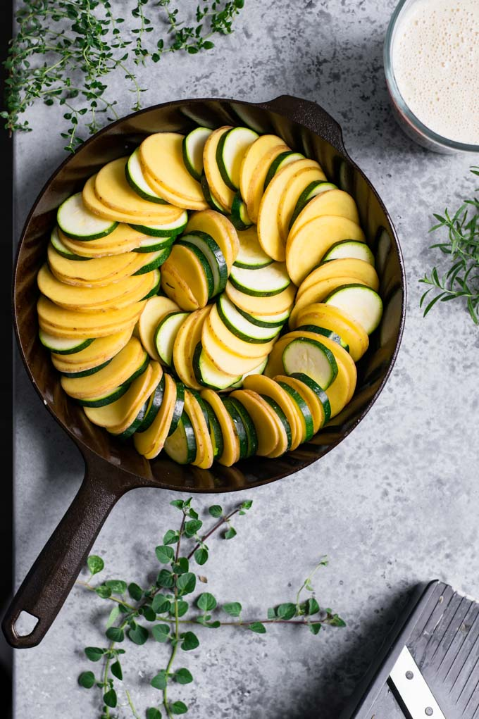 potato and zucchini arranged in a cast iron skillet, with the cream sauce and fresh herbs set off to the side