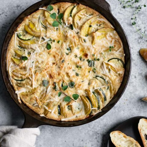 the potato and zucchini gratin just out of the oven, served with sliced baguette